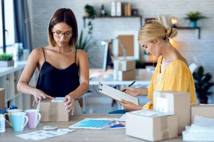 two freelance business women seller checking product order while packing and sealing cardboard boxes