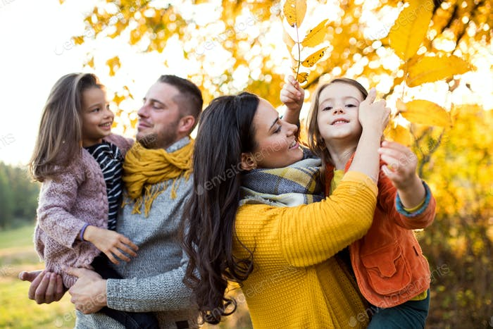 A portrait of young family with two small children in autumn nature