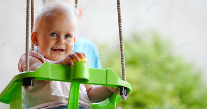 Happy baby enjoying outdoor activities and smiling while swinging