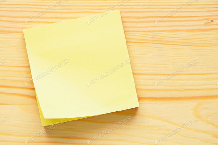 Yellow memo sticker on wooden wall