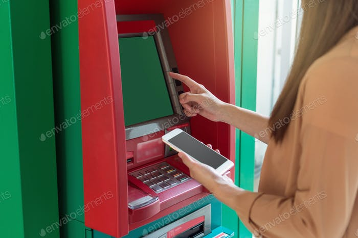 woman using the smart mobile phone for withdrawing in front of the ATM