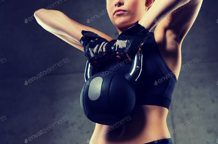 close up of woman with kettlebell in gym
