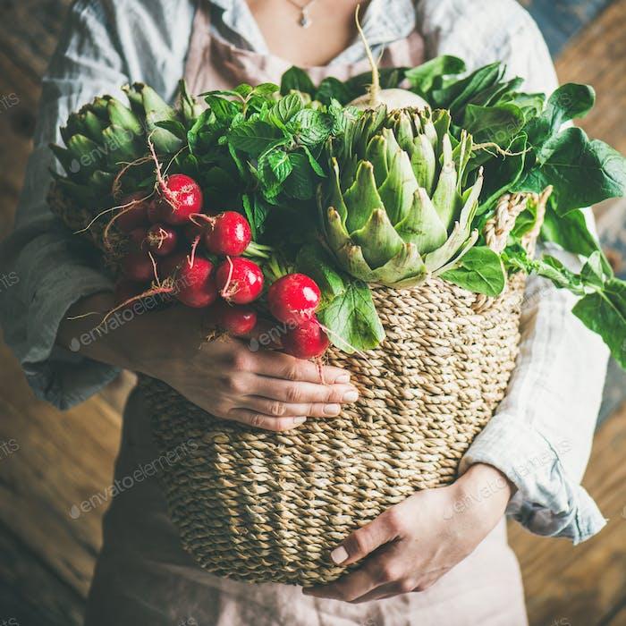 Female farmer holding basket with fresh vegetables, square crop