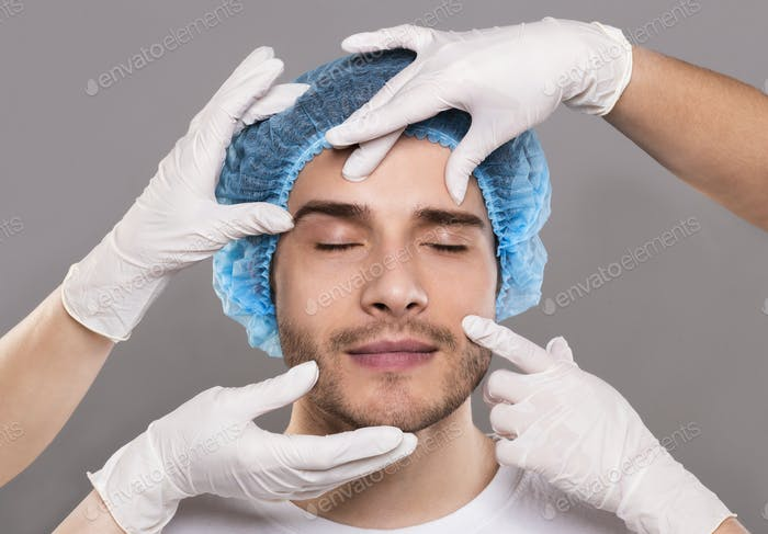 Doctor's hands in gloves checking face of young man
