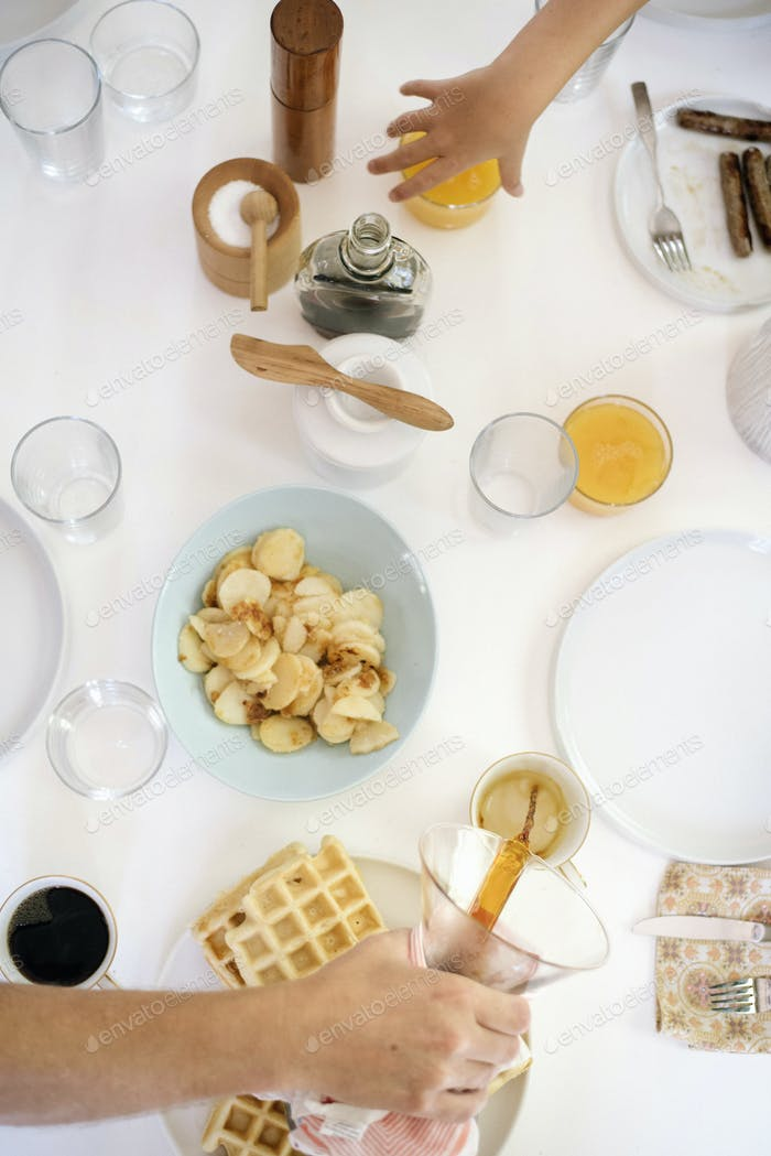 High angle view of a breakfast table, waffles, fried pototoes, coffee and juice.