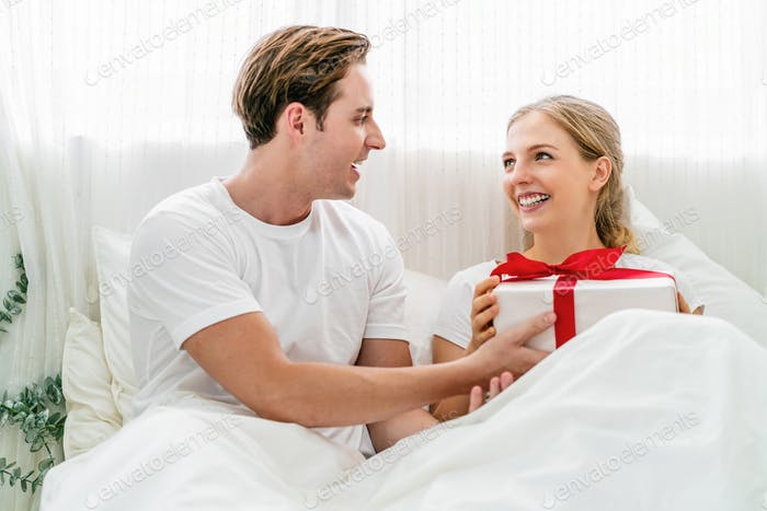 Caucasian Happy couple of lovers is celebrating together on the bedroom in home