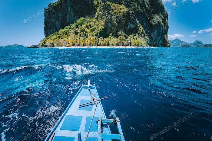 Traditional banca boat approach a small Ipil beach in front of circular Pinagbuyatan Island with