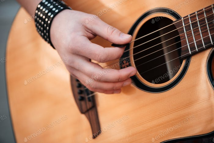 Male hands playing on guitar outdoors