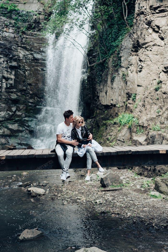 Un chico y una chica están sentados en un Puente