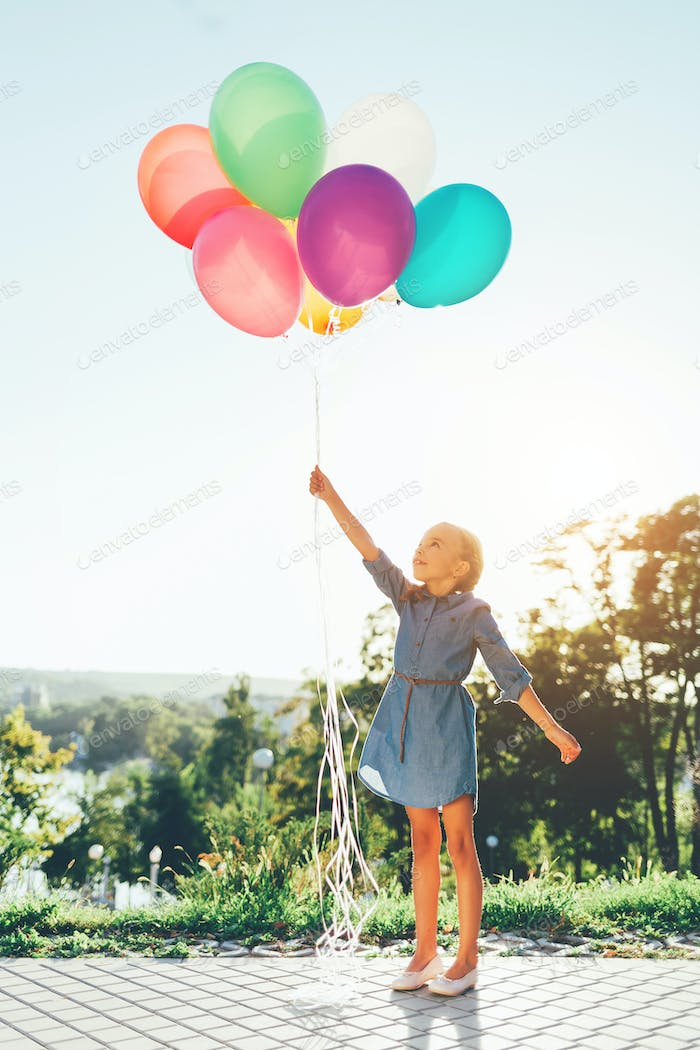 Girl holding colorful balloons stretching to the sky and dreamin