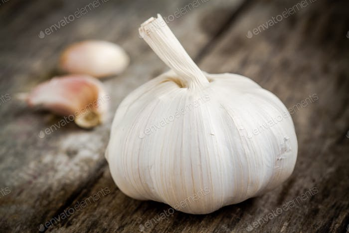 Organic garlic bulb with cloves close up on a wooden table