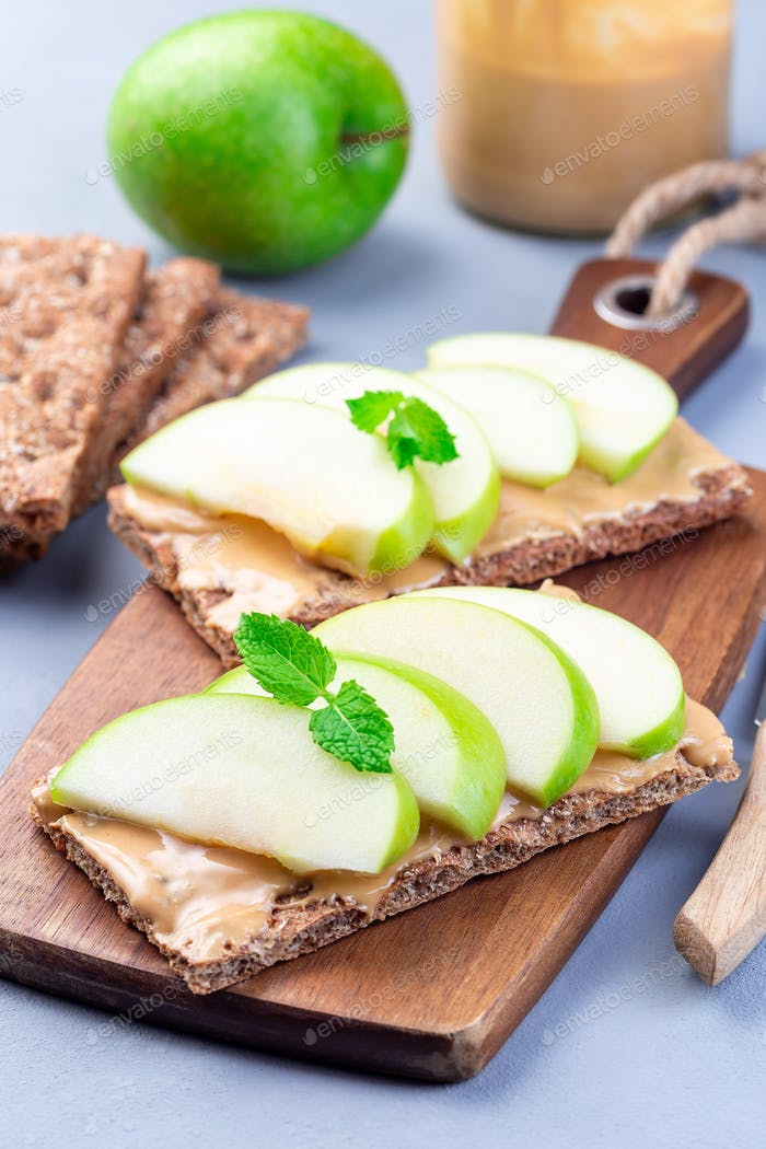 Sandwich with whole grain cracker, green apple slices and peanut butter, on  wooden board, vertical