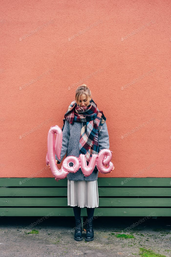 Elegant blonde woman in a large scarf and a grey coat holds an inflated ballon the word LOVE.