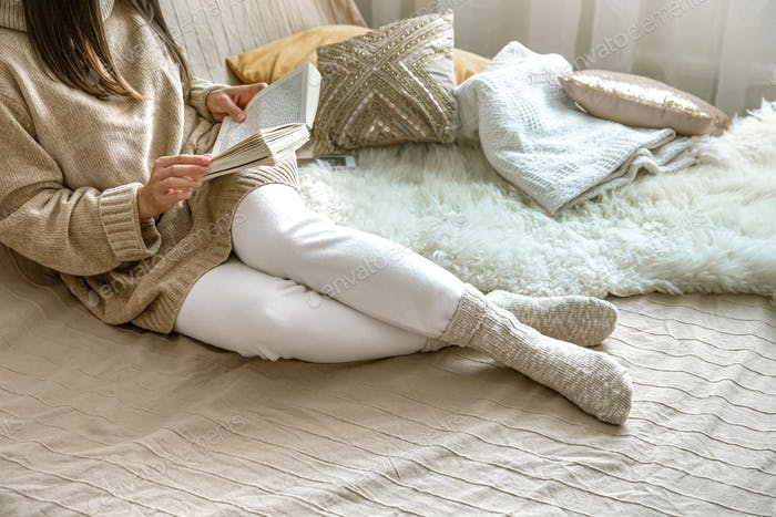 Cozy autumn or winter at home, a woman in a knitted sweater