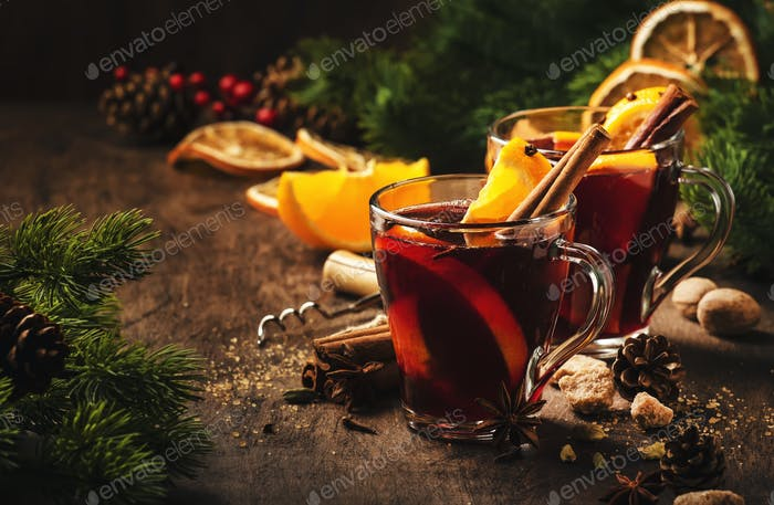 Xmas hot mulled red wine with spices and orange on wooden rustic table
