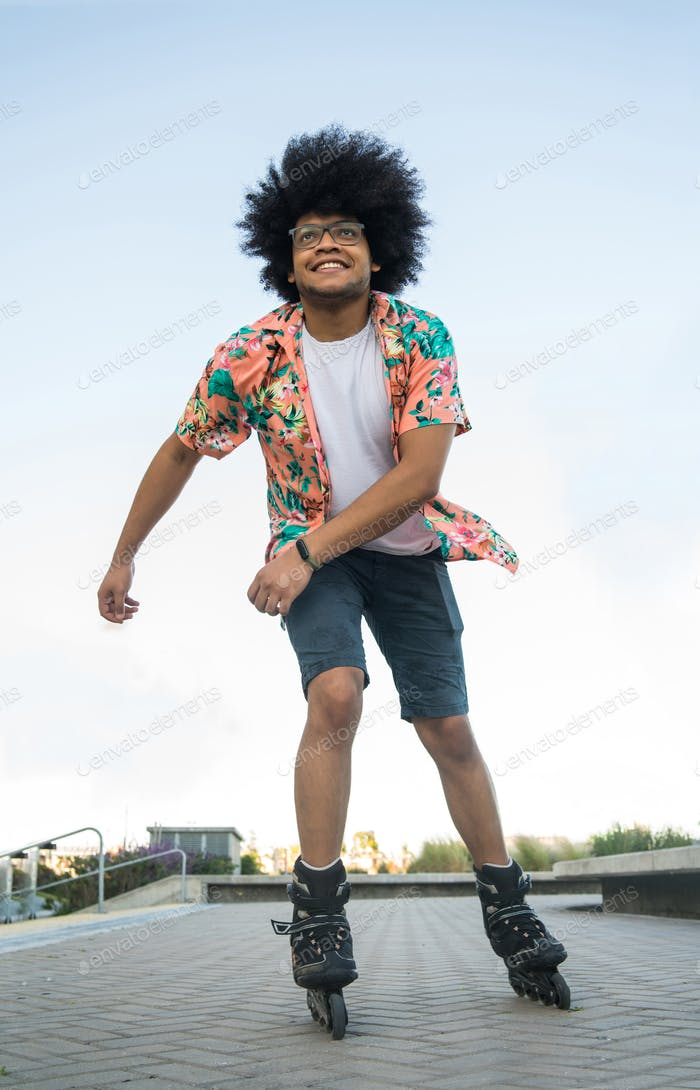 Latin man rollerskating outdoors.
