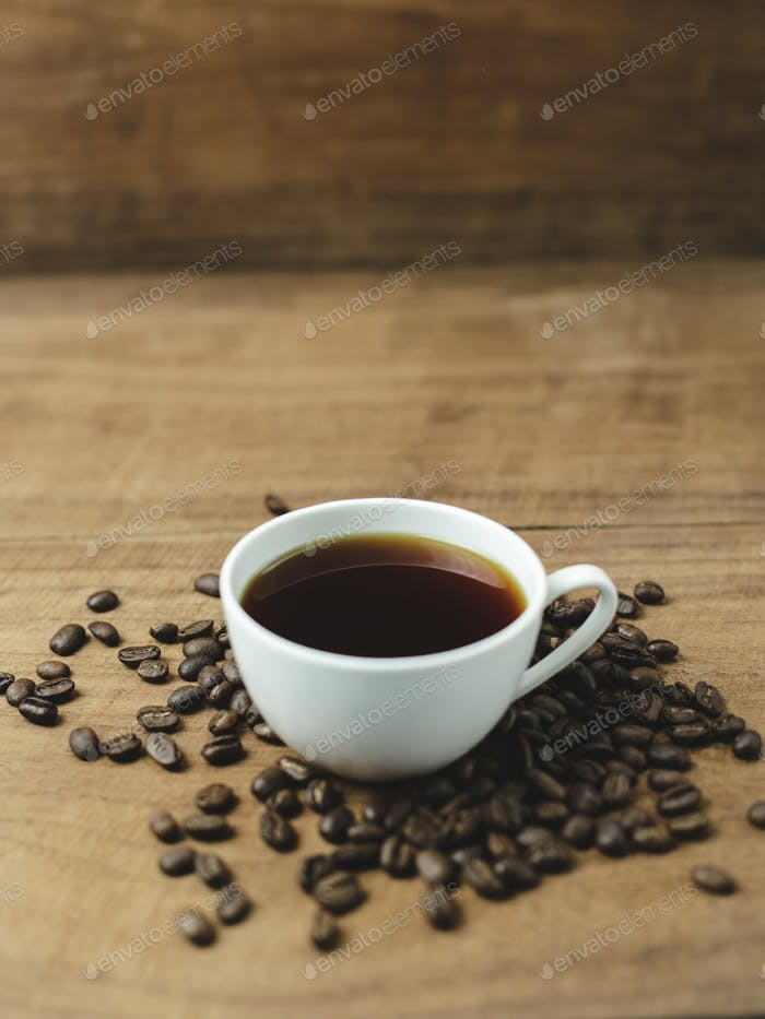 black coffee and coffee beans with wood background