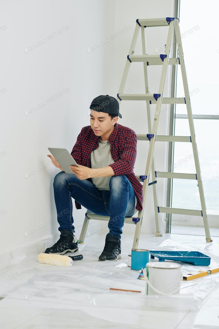 Man reading instruction before painting