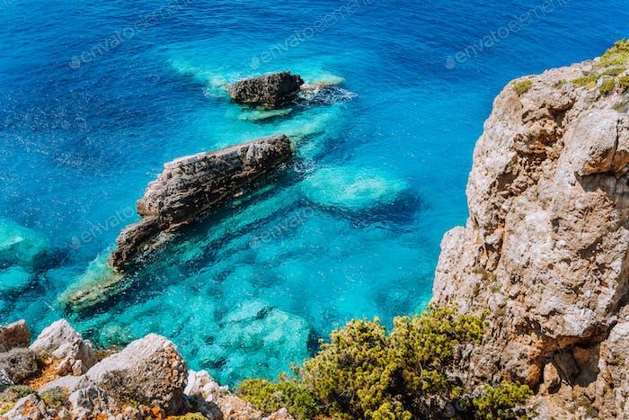 Rock cliffs and clear water at mediterranean sea coast. Greece