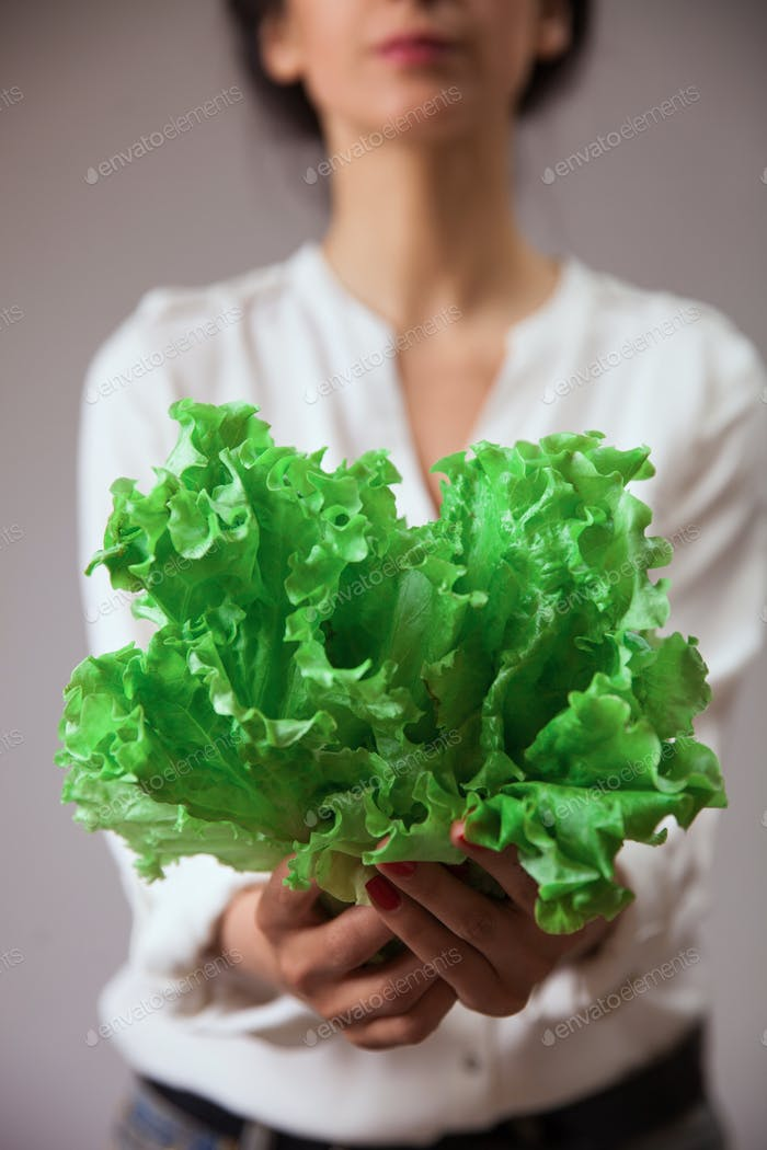 Young woman hands with salad leaves