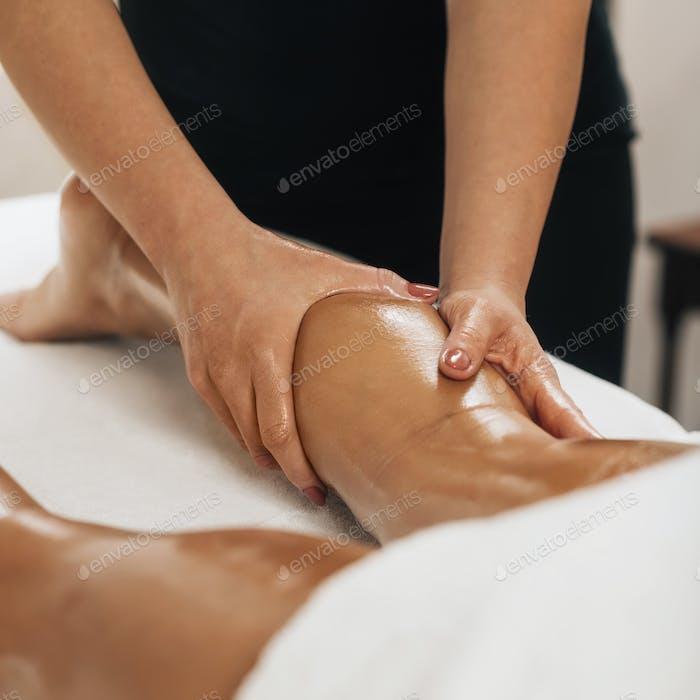 Anti Cellulite Massage. Masseuse Massaging a Female Calf
