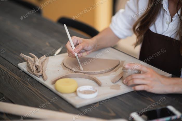 Woman's fingers adding and adjusting a clay part on a future ceramic product