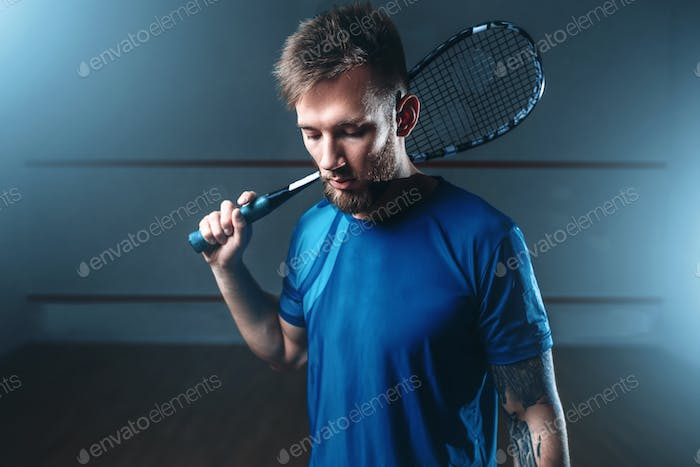 Squash player with racket, indoor training court