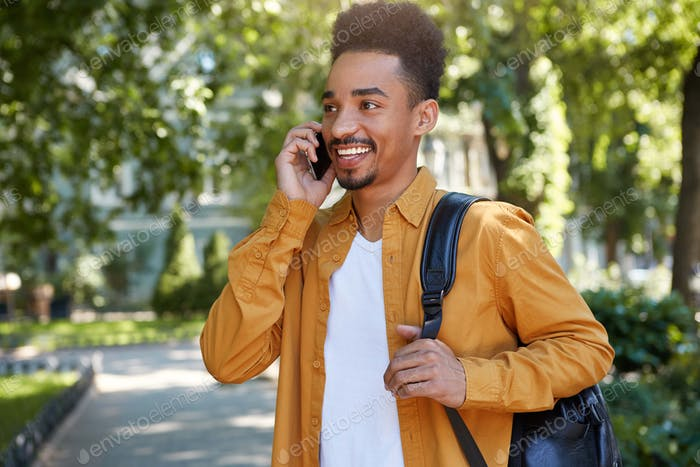 Young smiling dark skinned student walking at the park, speaking on smartphone
