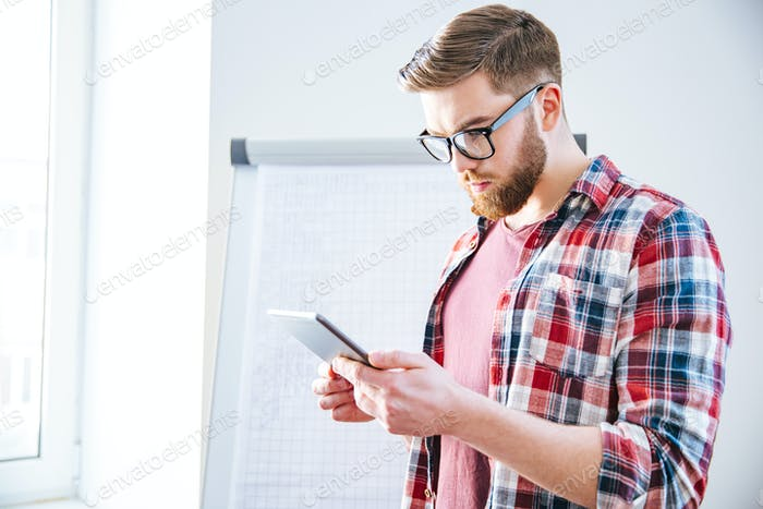 Handsome serious man with beard standing and using tablet