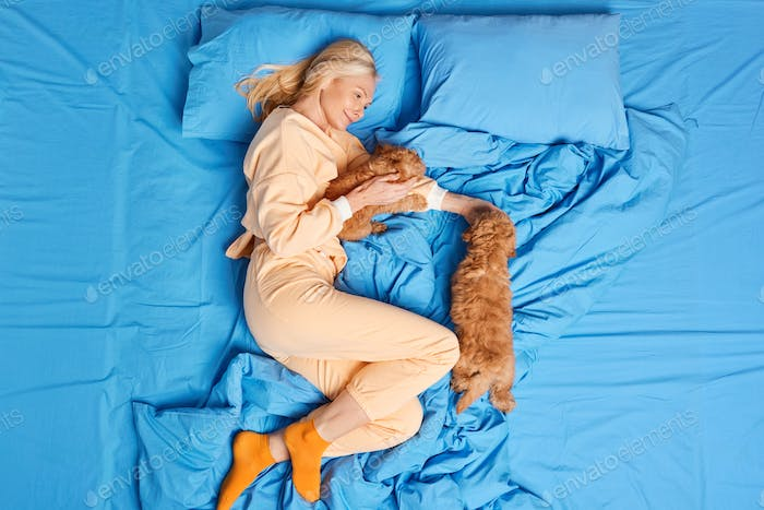 Top view of blonde middle aged European woman plays with two pedigree puppies dressed in pajama pose