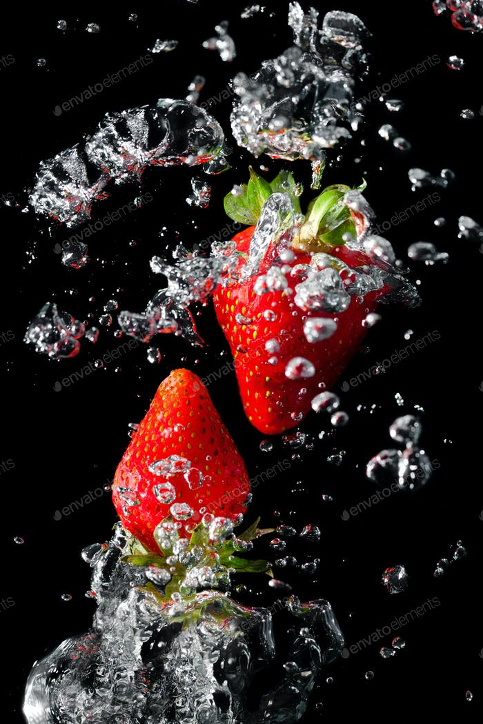 Two strawberries in the water with air bubbles