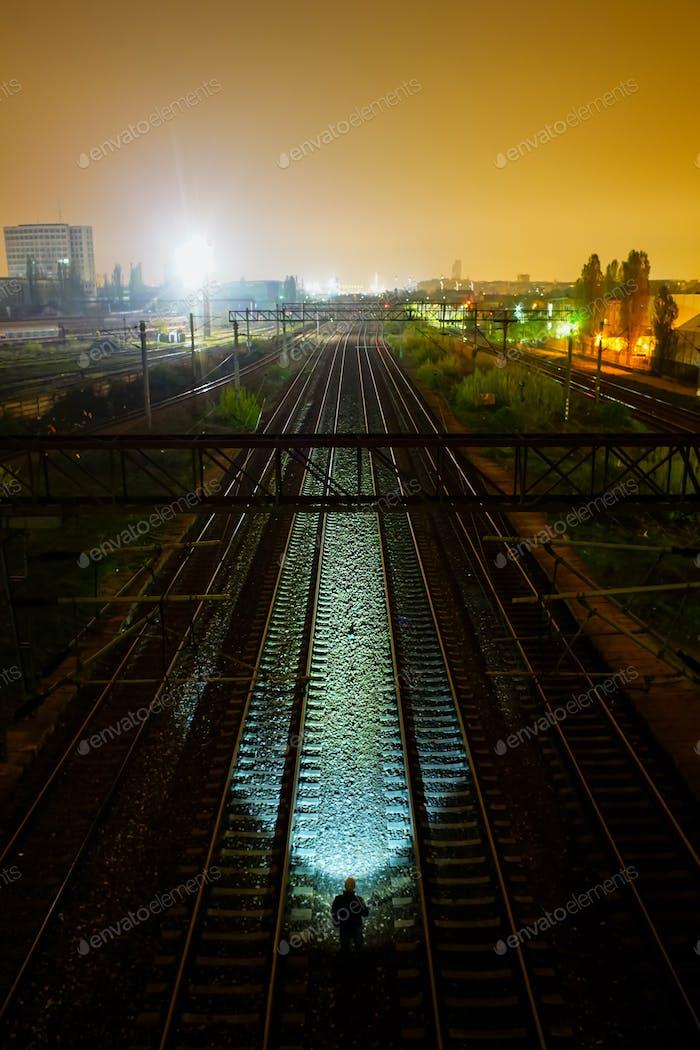 Man with flashlight illuminate train rails at night