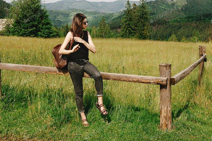Itylish Hipster Frau sitzend und Blick auf Berge