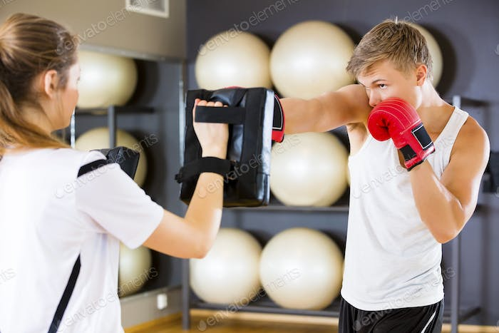 Dedicated Boxer Punching Bag Held By Instructor