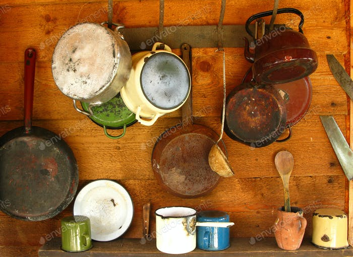 Old frying pans and cooking pots hanging on a wooden wall