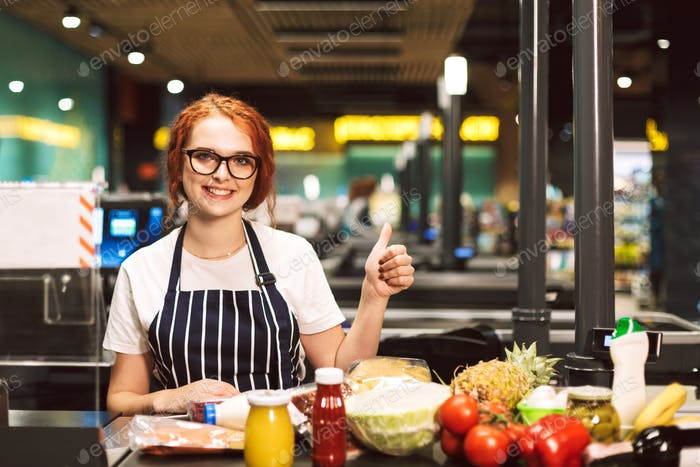 Young smiling female cashier in eyeglasses and striped apron wit