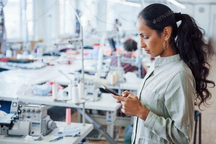 Женщина портница стоит на фабрике с телефоном в руках