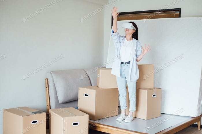 Young woman wearing VR glasses in new home