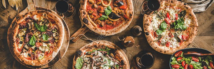 Italian pizza, fresh salad and red wine, wide composition