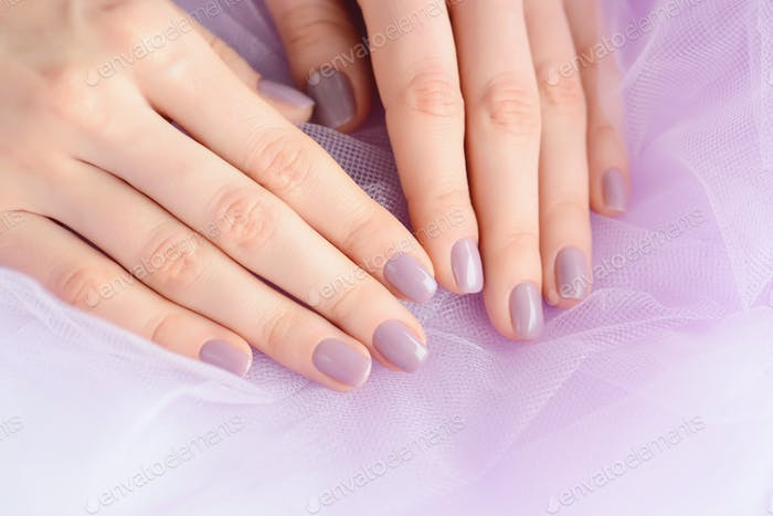 Closeup of hands of a young woman with pink manicure on nails ag