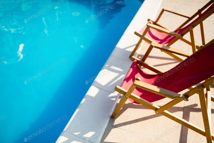 Deck chairs at side of pool