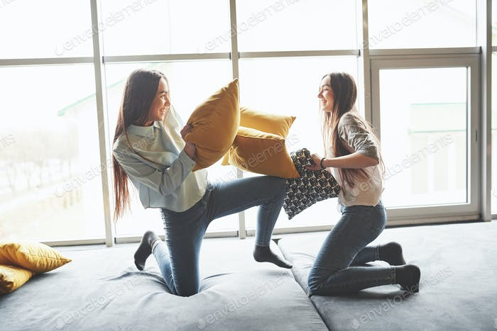 Two beautiful young twins sisters spending time together and are battling with pillows