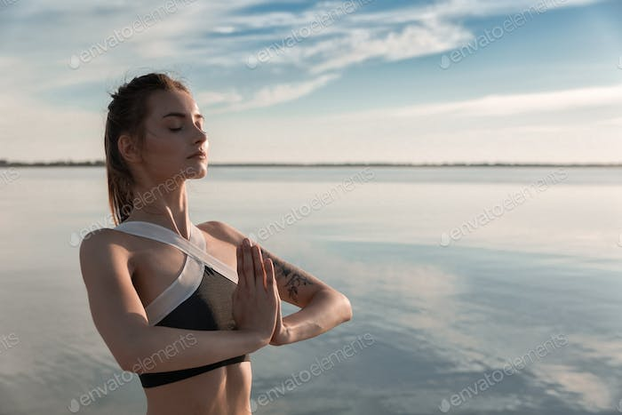 Sports beautiful woman at the beach meditation.