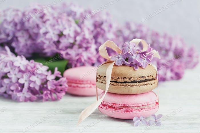 Cup of black coffee, lilac flowers and sweet pastel french macaroons