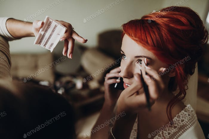 Stylish bride with red hair getting make up done by professional stylist
