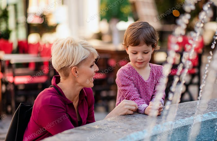 Mother with small daugther having fun outdoors in town