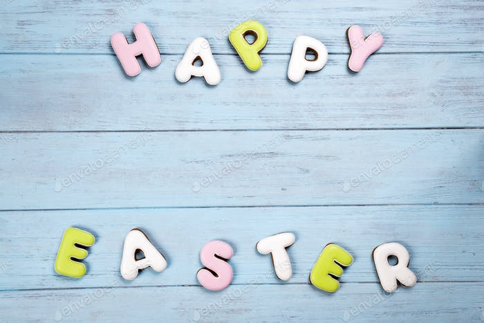 Lettering from cookies Happy Easter on wooden blue background.