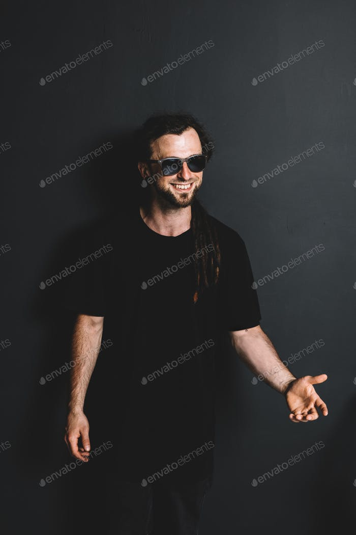 Happy young in sunglasses standing on a black background.