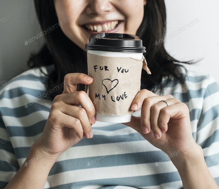 Closeup of Asian woman holding coffee cup