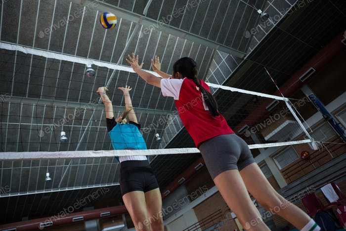 Female players playing volleyball in the court